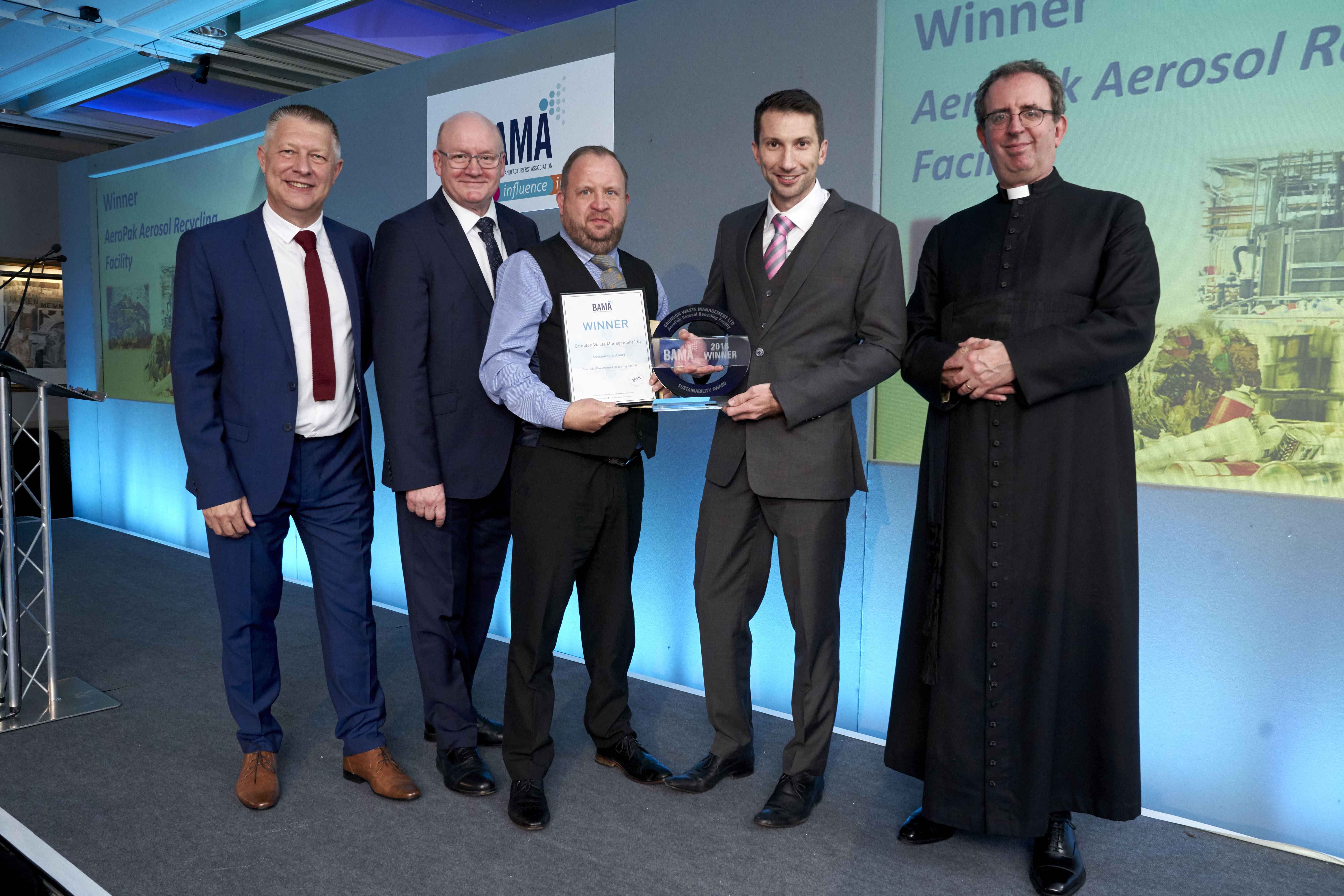 Grundon's Paul McConaghy and Tim Buxton celebrate winning the prestigious BAMA Sustainability Award 2018, which was presented to them by the Reverend Richard Coles.