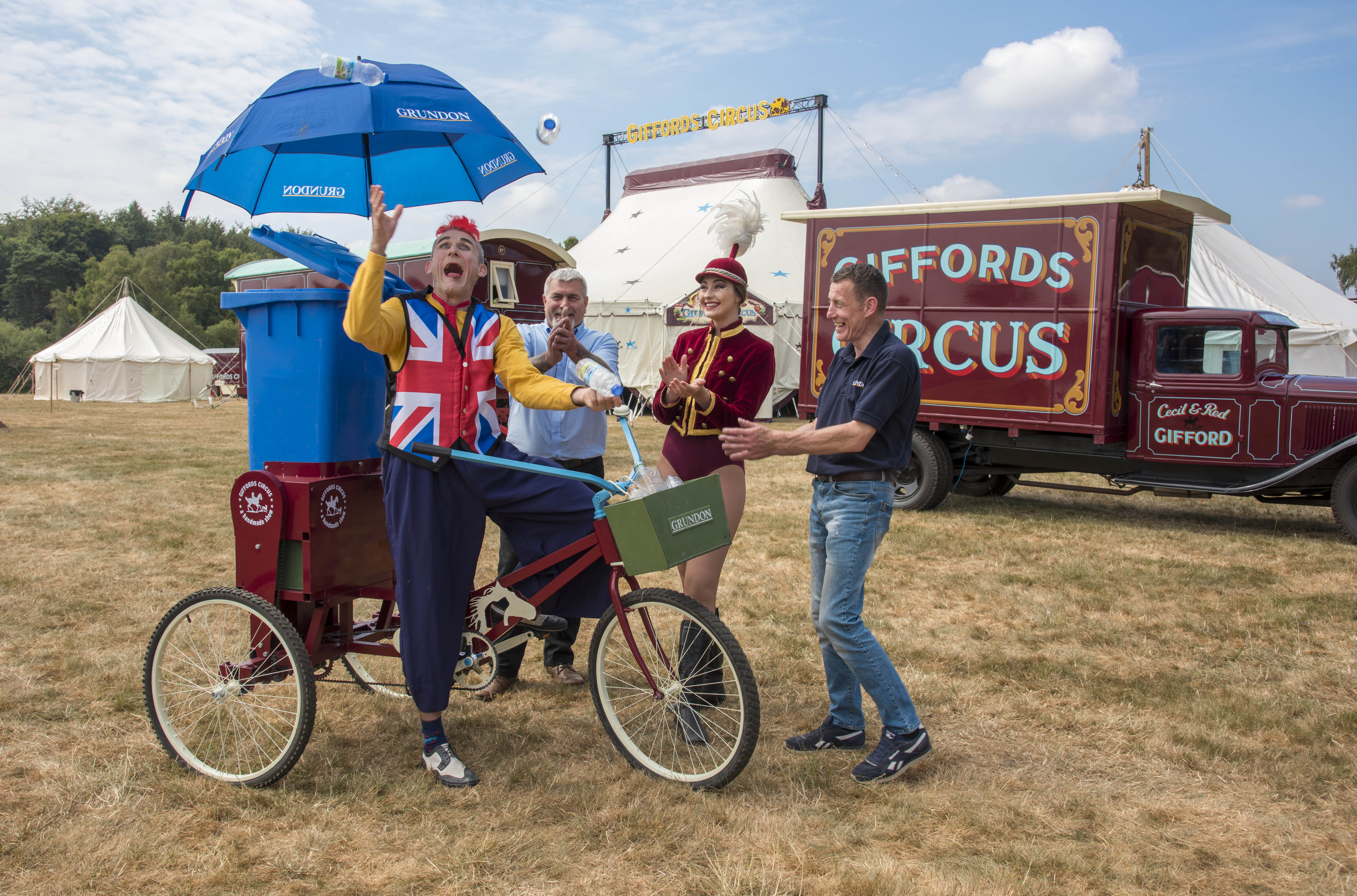 Tweedy shows off his juggling skills on the Recycle Bicycle watched by showgirl Lizzie and Grundon's Peter Kent (left) and Dave Forrest