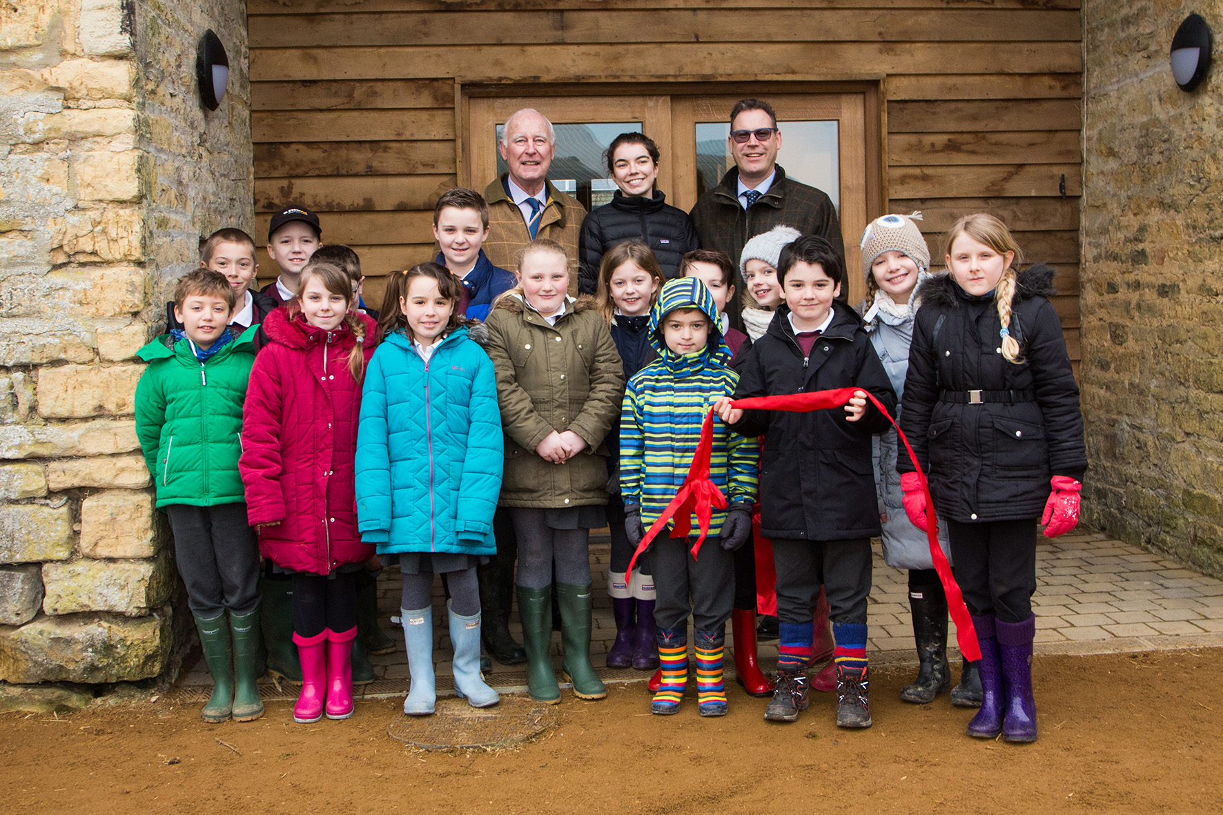 Norman Grundon, Chairman of Grundon Waste Management (back left) and Neil Grundon, Deputy Chairman (back right) celebrate the opening of the new education centre at Greystones Farm with children from Bourton-on-the-Water Primary School.