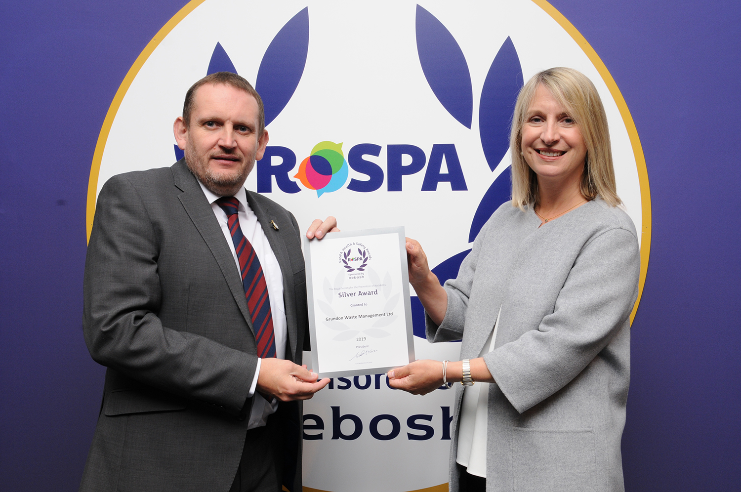 Reg Hodson, SHEQ Manager at Grundon Waste Management, collects the Silver Award from Jocelyn McNulty, RoSPA Trustee, at the RoSPA 2019 Awards