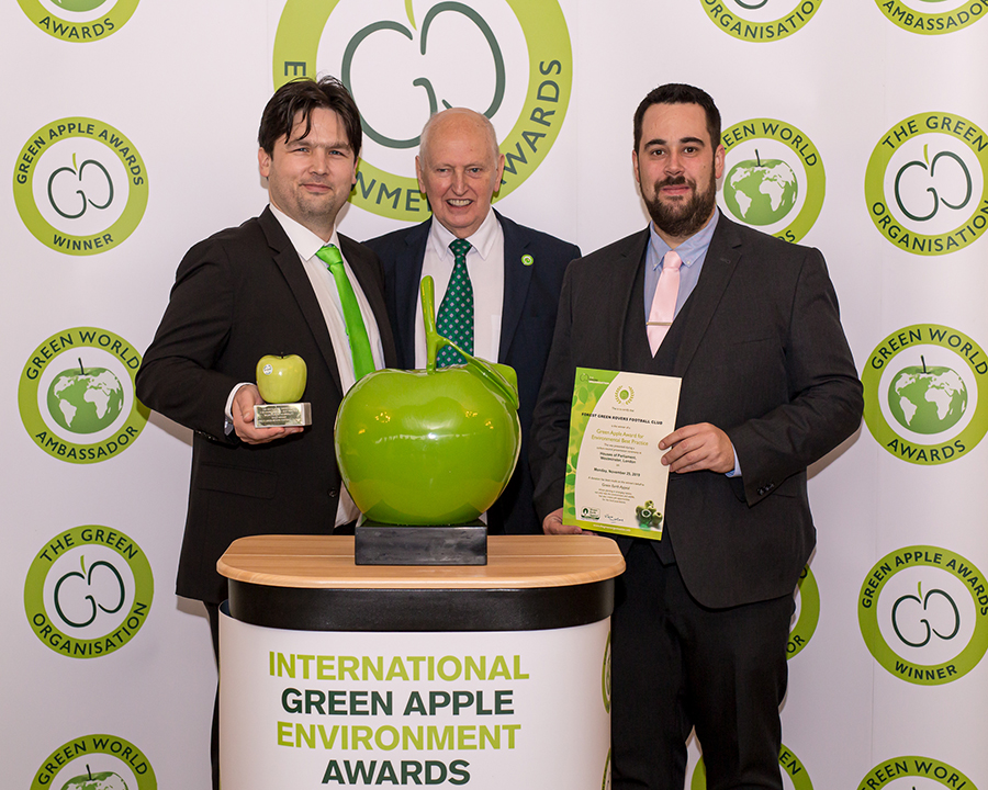 Forest Green Rover Football Club's General Manager, Dane Vince (left) and Daniel Peacey, Regional Sales Manager at Grundon Waste Management (right) collect the prestigious Gold Green Apple Award for Environmental Best Practice in the Sports Leisure & Hospitality wastes management category from Roger Wolens, Founder of The Green Apple Awards and Chief Executive Officer of The Green Organisation (centre)