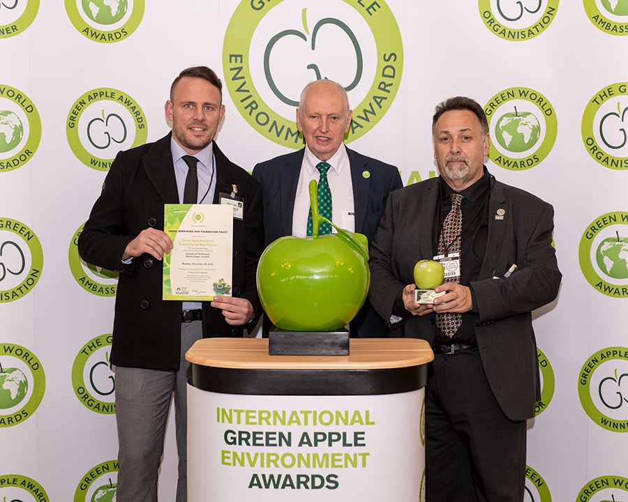 Grundon's Phil Steer, Commercial Manager – Clinical (left) and Steve Sellwood, Facilities Manager at the Royal Berkshire NHS Foundation Trust (right) collect the prestigious Gold Green Apple Award for Environmental Best Practice in the Wastes Management NHS and Healthcare category from Roger Wolens, Founder of The Green Apple Awards and Chief Executive Officer of The Green Organisation (centre)