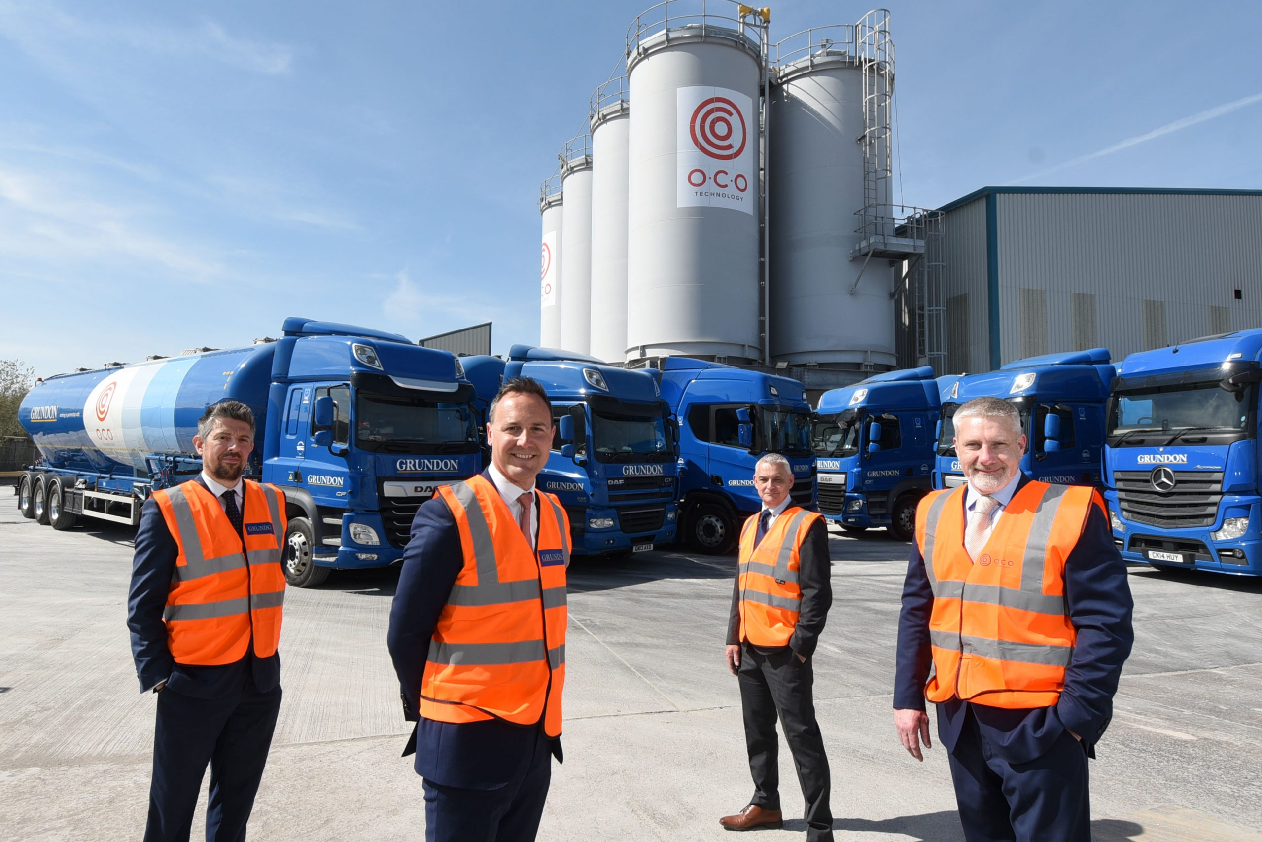Pictured at O.C.O's Avonmouth facility with the tanker fleet in the background, are (from left)  Richard Van-Den-Heule, Grundon's Depot Operations Manager at Bishop's Cleeve; Bradley Smith, Grundon's Sales & Marketing Director; Paul Barber, General Manager – Operations at O.C.O, and Steve Greig, O.C.O's Managing Director.