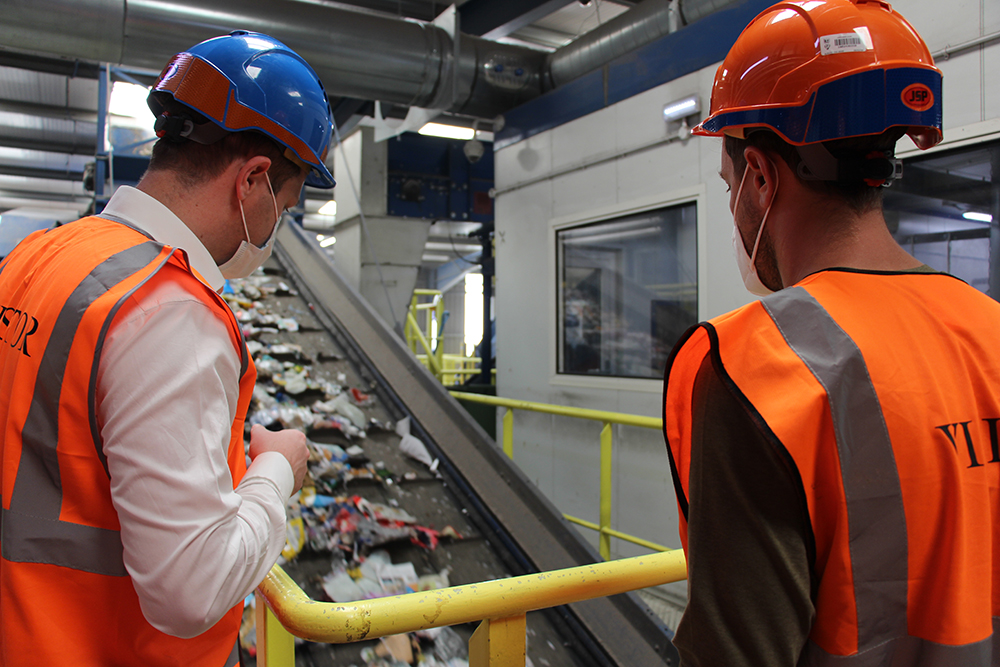 Owen George (left) shows Sebastian Vettel how Silverstone's waste is segregated ready for recycling at Grundon's Materials Recovery Facility.