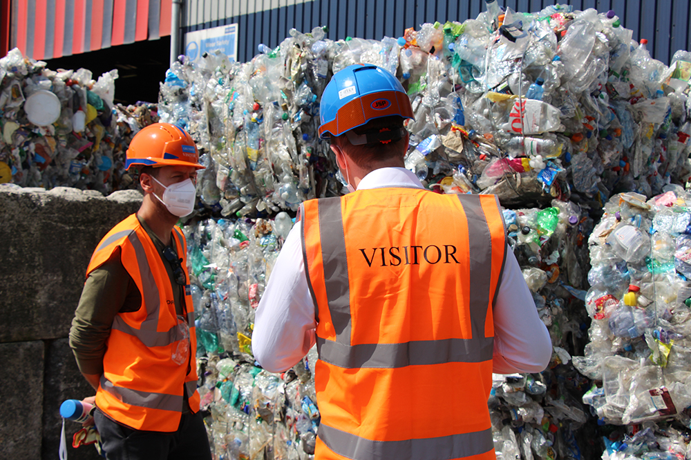 Sebastian Vettel (left) listens intently as Owen George explains the process of baling plastic bottles from Grundon's Materials Recovery Facility before they are sent for reprocessing.