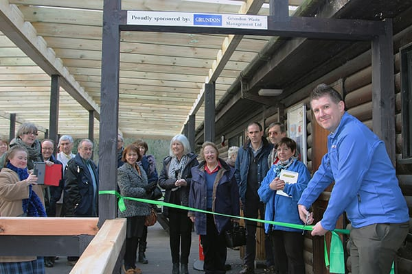 Officially open for business: Anthony Foxlee-Brown cutting the ribbon to open the veranda cheered on by Colne Valley Park Volunteers, local Councillors and representatives from Bucks Country Parks